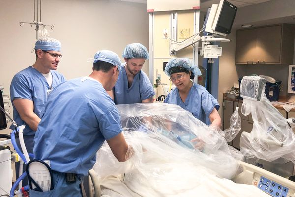 medical professionals work around a medical device